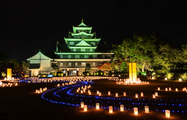 Château d'okayama avec des lanternes s'illuminant la nuit à okayama, au japon