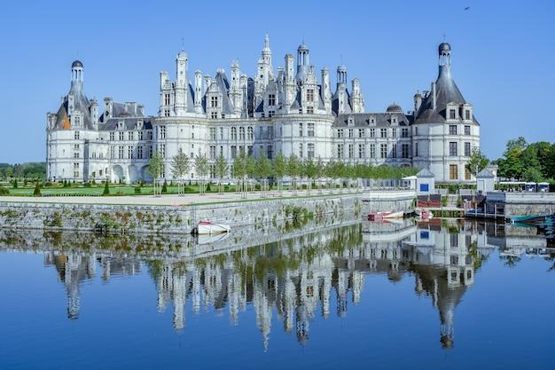 Le château se reflète dans le lac dans une journée ensoleillée château de chambord france en juillet