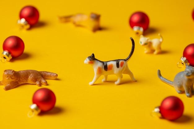 Des chats miniatures figurent à côté de boules de noël rouges sur une surface jaune