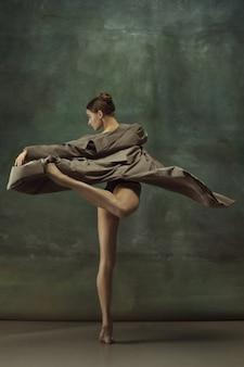 Chaud. danse de ballerine classique gracieuse, posant isolé sur fond de studio sombre. trench élégant. concept de grâce, de mouvement, d'action et de mouvement. semble en apesanteur, flexible. à la mode, stylé.