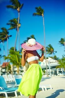 Chaude belle femme en chapeau de soleil coloré et robe marchant près de la plage océan sur une chaude journée d'été sur le sable blanc