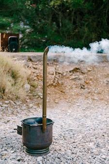 Chaudron en métal pour pilaf avec fumée de cheminée