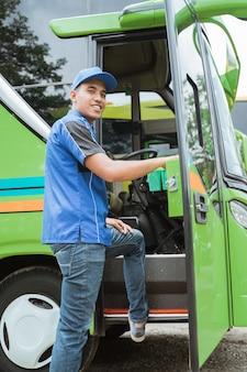 Un chauffeur de bus en uniforme et chapeau a souri à la caméra en entrant dans la porte du bus