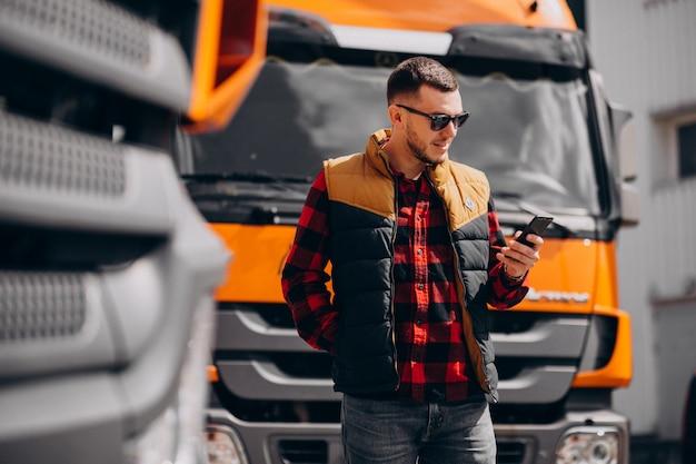 Chauffeur de camion de bel homme debout près du camion