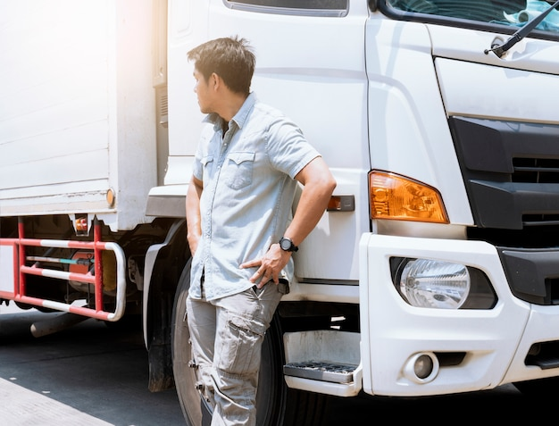 Un chauffeur de camion est debout avec un camion de fret