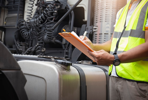 Un chauffeur de camion tenant un presse-papiers pour vérifier la sécurité d'un grand réservoir de carburant de camion semi.