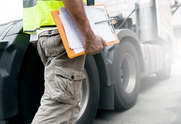 Chauffeur de camion tient un presse-papiers avec un camion semi.