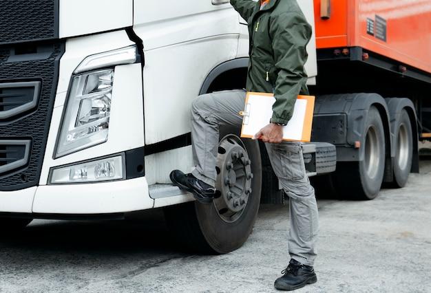 Chauffeur de camion tient un presse-papiers avec semi camion.