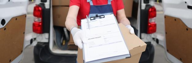 Le chauffeur du courrier portant un masque de protection médicale et des gants tient des documents avec un reçu de livraison