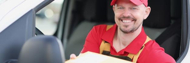 Le chauffeur du service de livraison propose un colis depuis sa camionnette