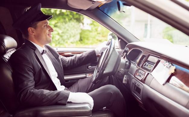 Chauffeur de limousine conduite et souriant