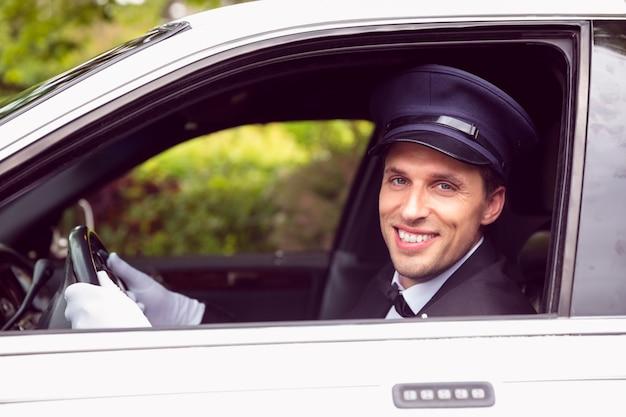 Chauffeur de limousine souriant à la caméra