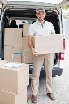 Chauffeur de livraison chargeant sa camionnette avec des boîtes