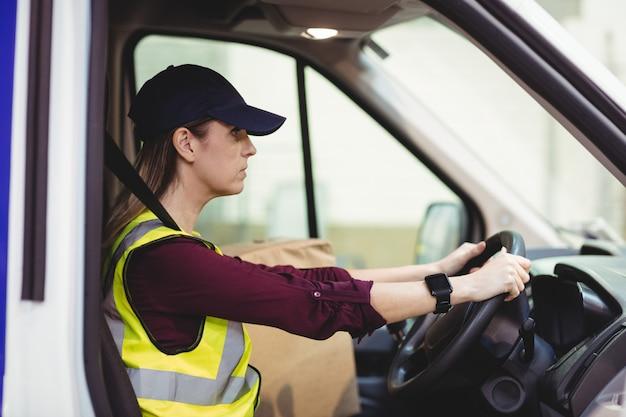Chauffeur-livreur conduisant une camionnette avec des colis sur le siège à l'extérieur de l'entrepôt