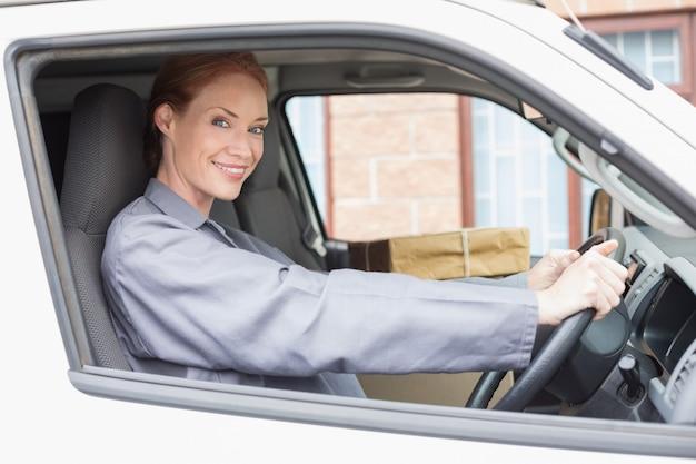 Chauffeur-livreur souriant à la caméra dans sa camionnette