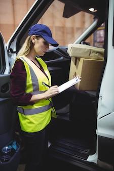 Chauffeur-livreur vérifiant sa liste sur le presse-papiers dans un grand entrepôt