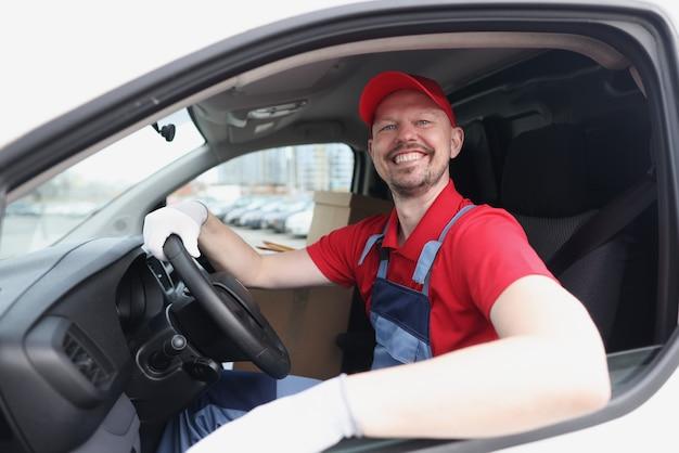 Un chauffeur de messagerie souriant est assis au volant d'une voiture