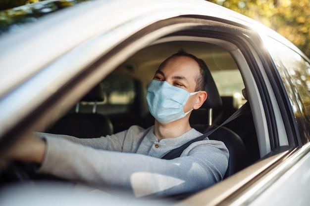 Un chauffeur de taxi conduit une voiture portant un masque médical lors d'une épidémie de coronavirus.
