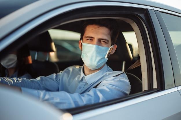 Chauffeur de taxi jeune garçon fait un tour au passager portant un masque médical stérile.