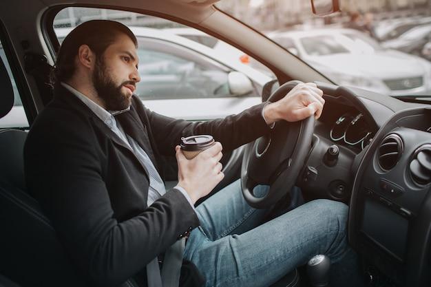 Le chauffeur va sur la route, parle au téléphone, travaille avec des documents en même temps. homme d'affaires faisant plusieurs tâches. homme d'affaires multitâche.