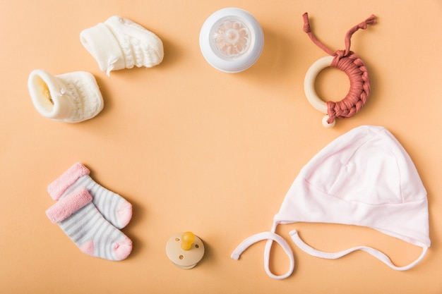 Chaussette de bébé; paire de chaussures en laine; sucette; casquette; bouteille de lait; jouet sur fond orange