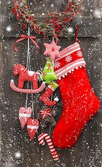 Chaussette de santas de décoration de noël et jouets faits à la main au-dessus du fond en bois rustique