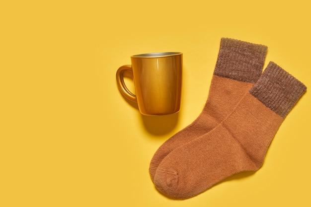 Chaussettes d'automne chaudes et tasse de café sur fond jaune