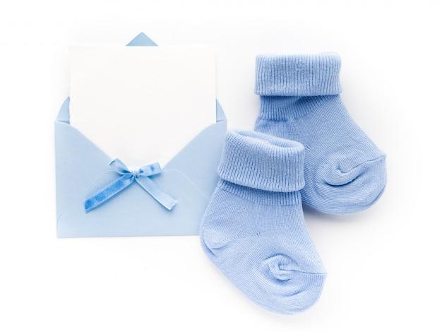 Chaussettes bleu petit garçon, carte vierge en enveloppe sur blanc. mise à plat.