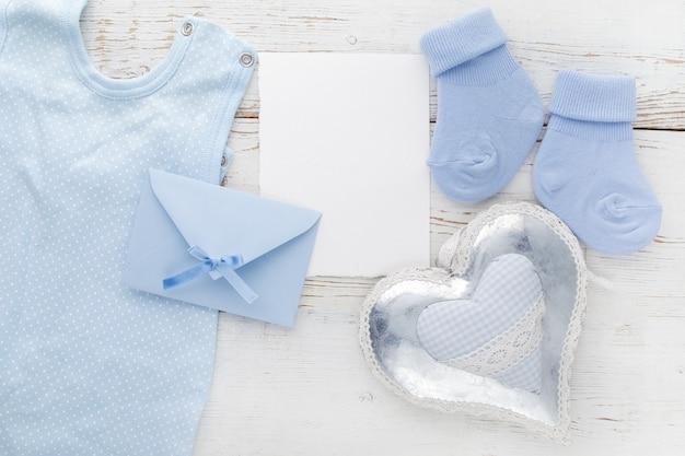 Chaussettes bleu petit garçon, carte vierge, enveloppe et coeur sur bois blanc. mise à plat.