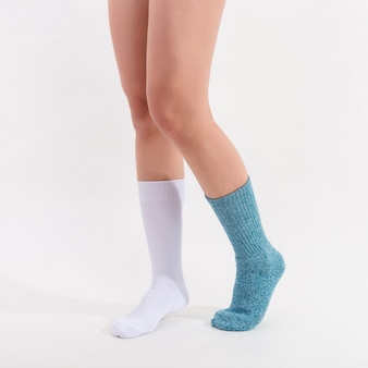 Chaussettes en coton blanc et bleu sur les pieds d'une femme magnifique. isolé sur fond blanc éclairage de studio.