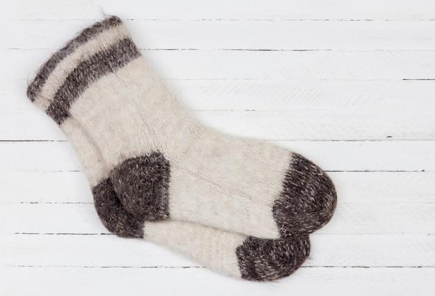 Chaussettes en fourrure de chien tricotées blanches sur bois blanc