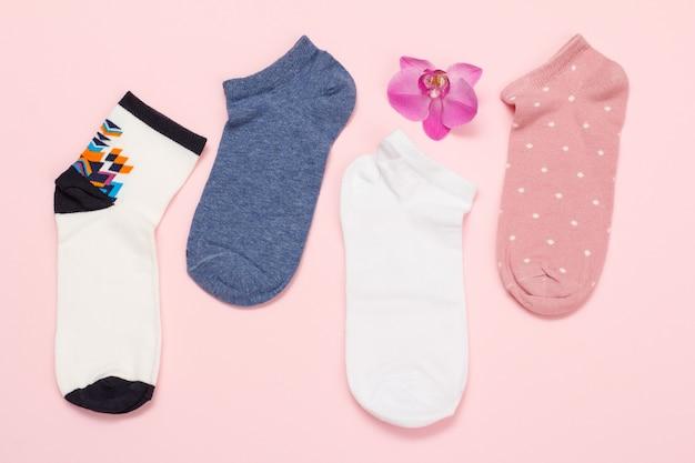 Chaussettes pour femmes et fleur d'orchidée sur fond coloré, vue de dessus.