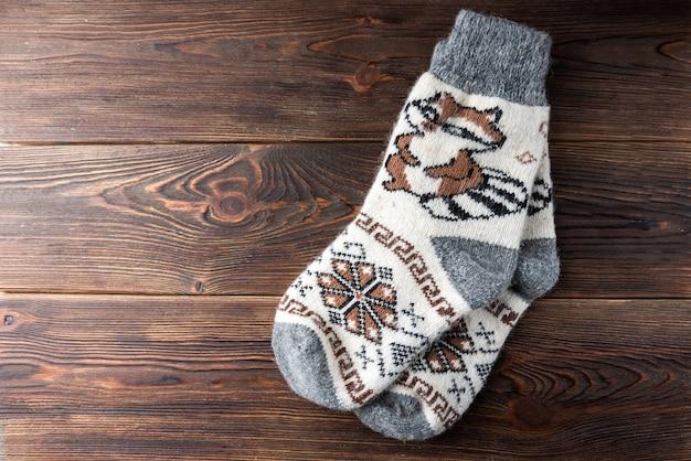 Chaussettes tricotées d'hiver avec raton laveur sur fond de bois