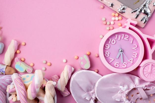 Chaussons de ballet, bonbons et montres sur fond rose.