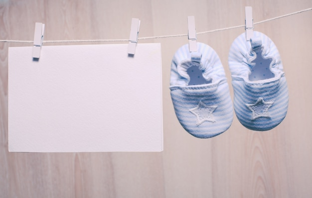Chaussons bébé garçon attachés à la corde et carte vierge pour les salutations