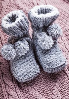 Chaussons bébé en laine tricotée avec pompons close up