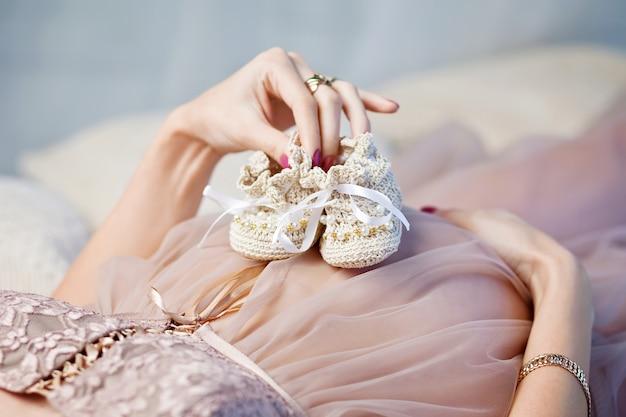 Chaussons de bébé nouveau-né dans les mains des mères. ventre de femme enceinte image en gros plan.