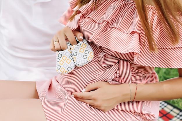Chaussons de bébé nouveau-né dans les mains des parents et ventre de femme enceinte.