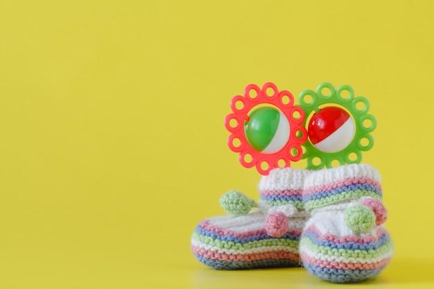 Chaussons bébé tricotés sur fond jaune uni