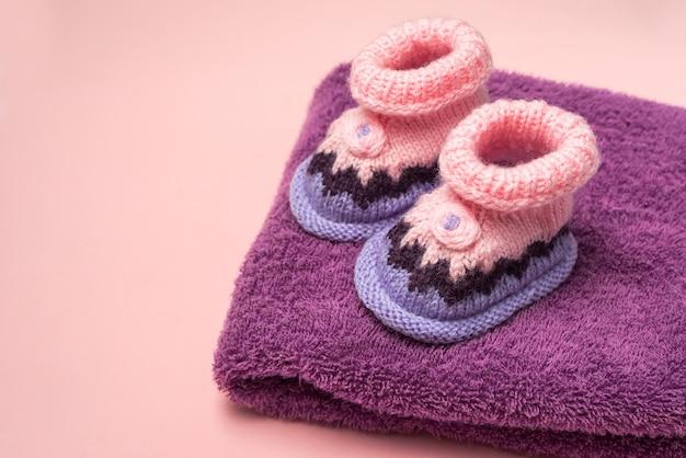 Chaussons bébé tricotés sur fond rose et une serviette éponge violette
