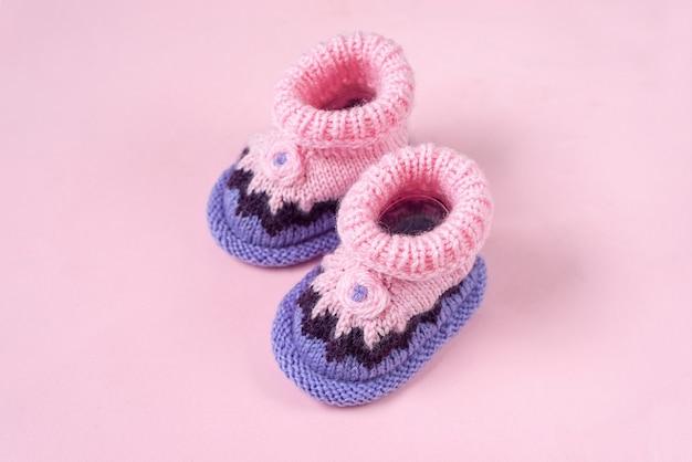 Chaussons bébé tricotés sur fond rose