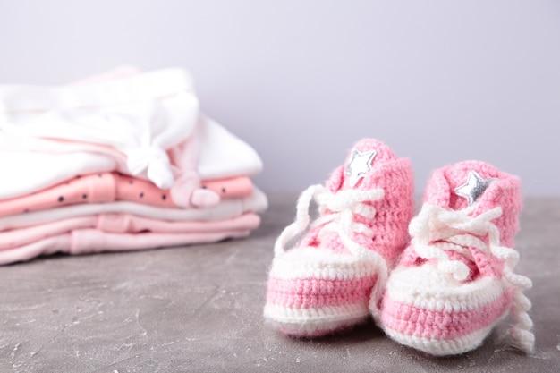Chaussons bébé avec des vêtements sur gris