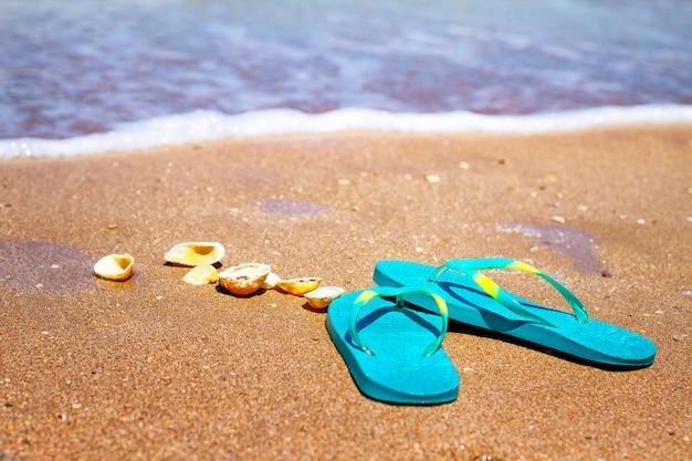 Chaussons bleus se tiennent sur le sable au bord de la mer