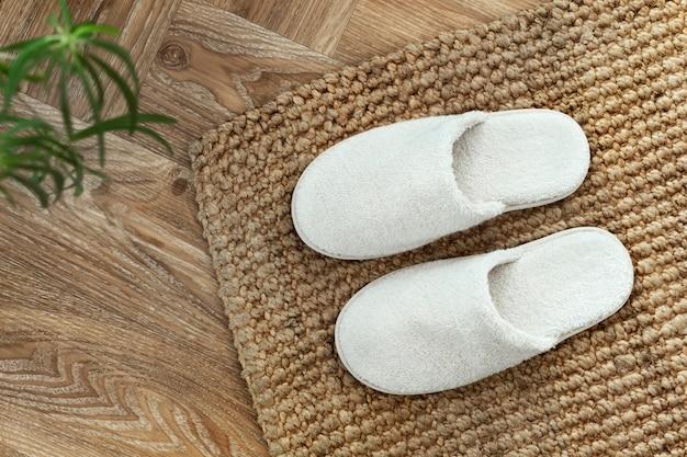 Chaussons d'intérieur blancs sur tapis de jute