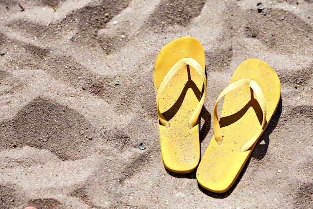 Chaussons de plage jaunes sur la plage de sable fin, été, baignade