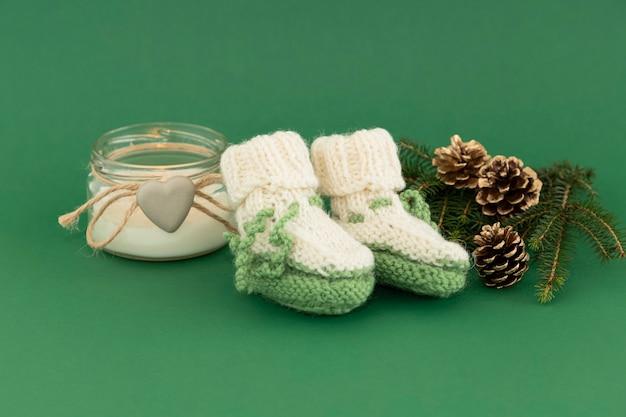 Chaussons verts pour un nouveau-né à noël avec des bougies et une branche de sapin.