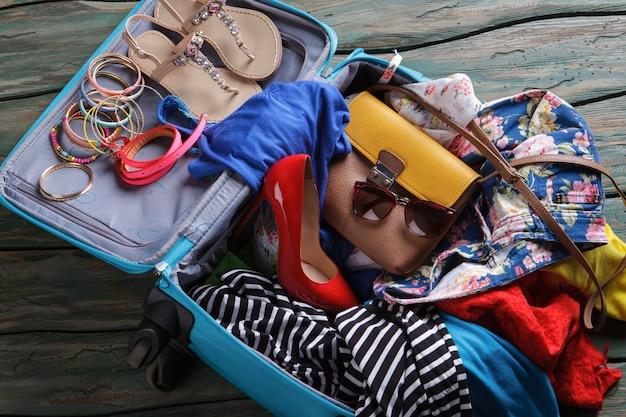 Chaussure à talon rouge dans une valise. vêtements froissés dans un sac à bagages. il n'y a jamais assez de place. pensez à acheter une valise plus grande.