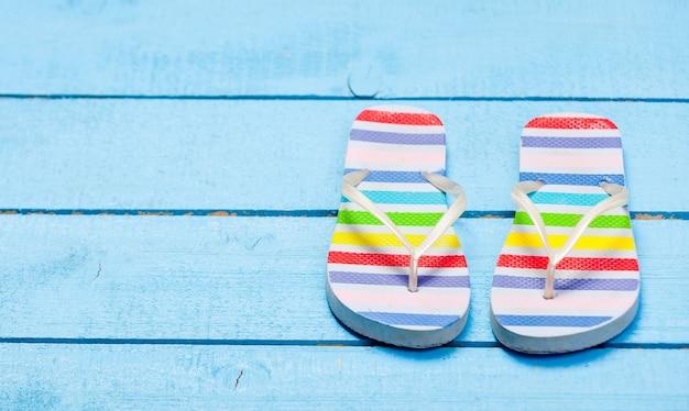 Chaussure tongs colorées sur bois bleu
