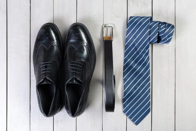 Chaussures et accessoires pour hommes étendus sur le plancher en bois