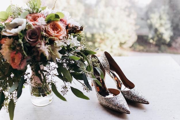 Des chaussures en argent étincelantes pour la mariée se tiennent sur le rebord de la fenêtre sous le bouquet de mariage riche